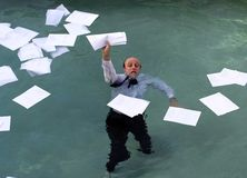 But the report doesn't lie. Businessman in swimming pool about to drown in paperwork, floating all around him is his paperwork stock photo