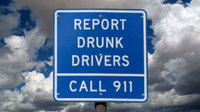 Report Drunk Drivers Sign with Time Lapse Clouds. Report drunk drivers highway sign with time lapse clouds