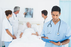 Report reading with colleagues and patient behind Stock Images
