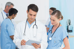 Report reading with colleagues and patient behind Stock Photography
