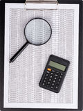 The report table under magnifying glass with calculator Stock Photo