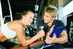 Report on training. Woman with dumbbells in a gym, her personal trainer gives a report on her training Stock Photos