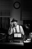 Reporter che lavora tardi alla notte e che fuma nel suo ufficio Immagini Stock