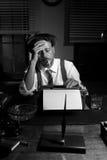 Reporter che lavora tardi alla notte e che fuma nel suo ufficio Fotografia Stock
