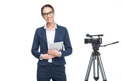 reporter de télévision féminin de sourire à l'aide du comprimé numérique tenant la caméra vidéo proche, image stock