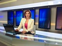 Reporter della TV allo scrittorio di notizie immagini stock