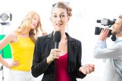 Reporter, der ein Interview auf Filmkulisse mäßigt Lizenzfreie Stockfotos