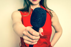 Reporter femminile con il microfono nero che fa intervista fotografie stock