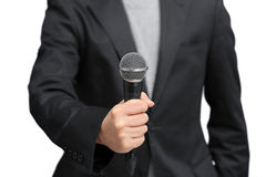 Reporter grabbing microphone with hand to interview. Isolated white background Royalty Free Stock Image