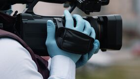 Reporter holding the camera with the latex gloves. Reporting about covid-19 outbreak. Close up
