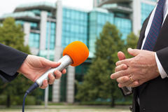 Reporter holding microphone interviewing businessman or politician Royalty Free Stock Photography