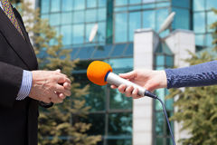 Reporter interviewing businessman, corporate building in background Stock Photos