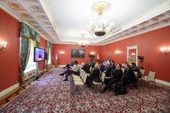 Reporter lyssnar och skriver information på förstorat möte Royaltyfri Bild