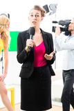 Reporter moderating an interview. Reporter and cameraman shoot actress interview on film set for TV or Television stock images