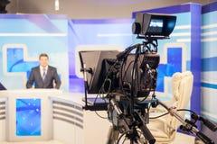 Reporter o anchorman maschio della registrazione della cinepresa di televisione Radiodiffusione in tensione fotografia stock