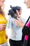 Reporter och kameraman skjuter en intervju Royaltyfria Bilder