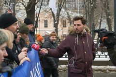 Reporter of the Russian TV Rain channel Aleksei Korostelev interviewing demonstrators carrying a political banner. Moscow, Russia - February 24, 2019. Nemtsov stock photography