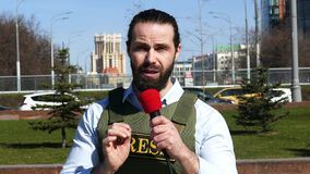 Reporter`s arm with a microphone wearing a vest