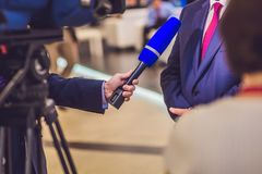 The reporter`s hand holds the microphone. Takes an interview.  Royalty Free Stock Images