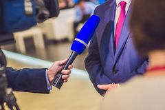 The reporter`s hand holds the microphone. Takes an interview.  Royalty Free Stock Photo