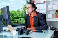 Reporter som arbetar i redaktörs- kontor med datoren Royaltyfria Bilder