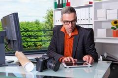 Reporter som arbetar i redaktörs- kontor med minnestavladatoren Fotografering för Bildbyråer