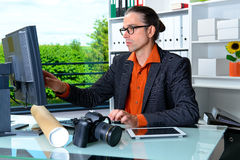 Reporter working in editorial office with computer. Young reporter working in editorial office with computer Royalty Free Stock Images