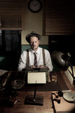Reporter working late at night and smoking in his office Royalty Free Stock Image