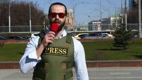 Reportero con un micrófono que lleva un chaleco almacen de video