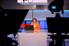 Reportero de la TV en el escritorio de las noticias Foto de archivo libre de regalías