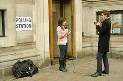 Reportero en el colegio electoral durante la elección general Foto de archivo