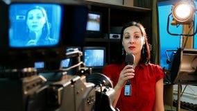 Reportero real de las noticias de la TV delante de la cámara de vídeo