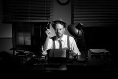 Reportero retro que trabaja tarde y que fuma Foto de archivo libre de regalías