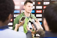 Reporters Interviewing Young Man. Portrait of handsome young sportsman giving interview to group of journalists during press conference Stock Photography