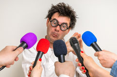 Reporters making interview with funny scientist Stock Photos