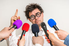 Reporters making interview with funny scientist. Reporters with microphones making interview with funny scientist - journalism and broadcasting concept Royalty Free Stock Photography