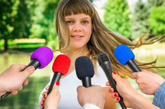 Reporters making interview with young woman Royalty Free Stock Photo