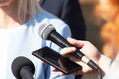 Reporters making media interview with business woman or female politician stock image