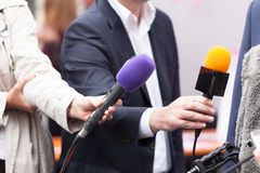 Reportes holding microphones, conducting media interview Royalty Free Stock Photos