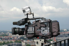 Reporting. Professional high definition television-camera aimed at the city, ready to report stock images
