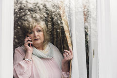 Reporting A Crime. Senior woman is reporting a neighborhood crime to the police on the phone. She is looking out her window Royalty Free Stock Photography