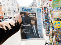 Reporting handover ceremony presidential inauguration of  Emmanu. PARIS, FRANCE - MAY 15, 2017: Man buys L`Ami French newspaper reporting handover ceremony Stock Image