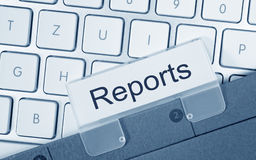 Reports - folder with text on computer keyboard. In the office stock photo