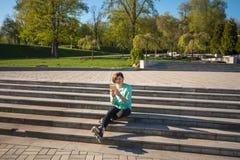 Repos étonnants de fille après avoir fait du patin à roulettes Photographie stock libre de droits