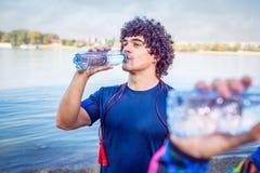 Repos après que le Séance d'entraînement-homme boive l'eau pour compléter le niveau de l'énergie photo libre de droits