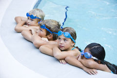Repos d'enfants, s'arrêtant du côté de la piscine Image libre de droits