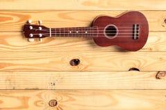 Repos d'ukulélé de Brown sur un plancher en bois images stock