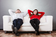 Repos de détente de couples heureux sur le divan à la maison Photo stock
