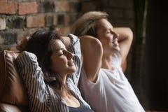 Repos de rêverie de couples heureux sur le divan pendant le week-end Photo stock