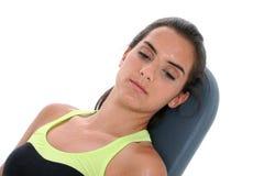 Repos de transpiration de belle fille de l'adolescence sur le banc de séance d'entraînement Photos stock